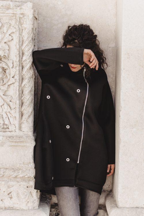 dekonstruirani crni kaput, od materjala ronilackog odijela, sa srebrnim ukrasima, kopca se na patent, ima džepove, iz nove kolekcije.